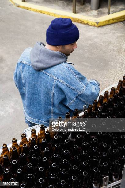 Man standing next to conveyor belt with bottles