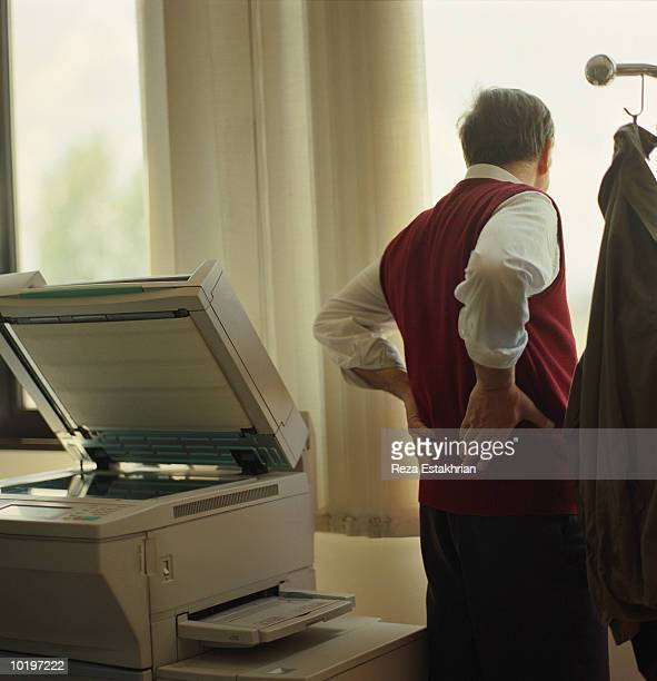Man standing next to copy machine, looking out window, rear view