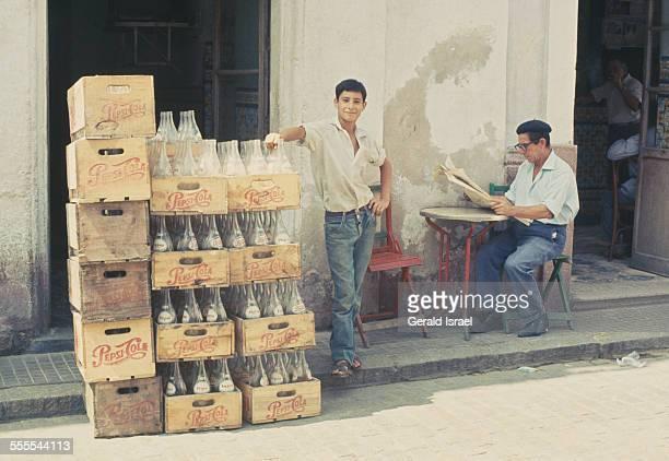A man standing next to crates containing empty Pepsi bottles in El Puerto de Santa María Cádiz Spain circa 1960