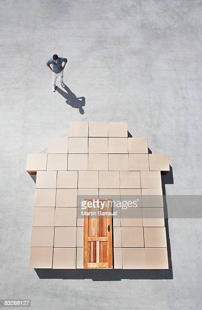 Man standing next to house outline on sidewalk