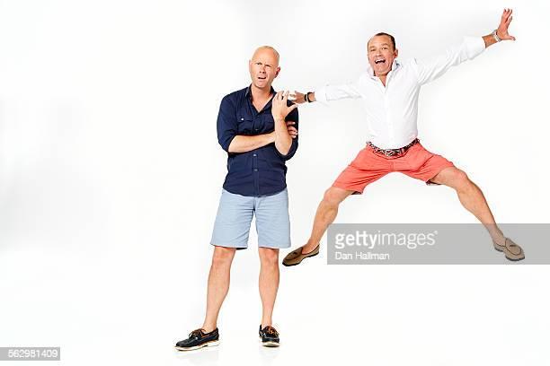 Man standing next to man jumping
