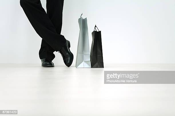 man standing next to shopping bags, cropped view of feet, low angle view - mens dress shoes stock pictures, royalty-free photos & images