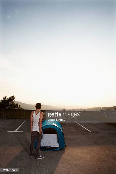 Man standing next to tent in parking lot