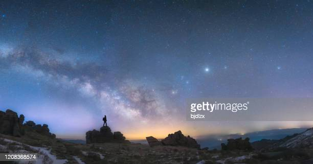 a man standing next to the milky way galaxy - wide stock pictures, royalty-free photos & images