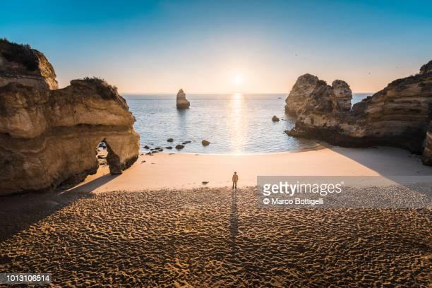 man standing on a beach at sunrise. high angle view. algarve, portugal. - mid distance stock pictures, royalty-free photos & images