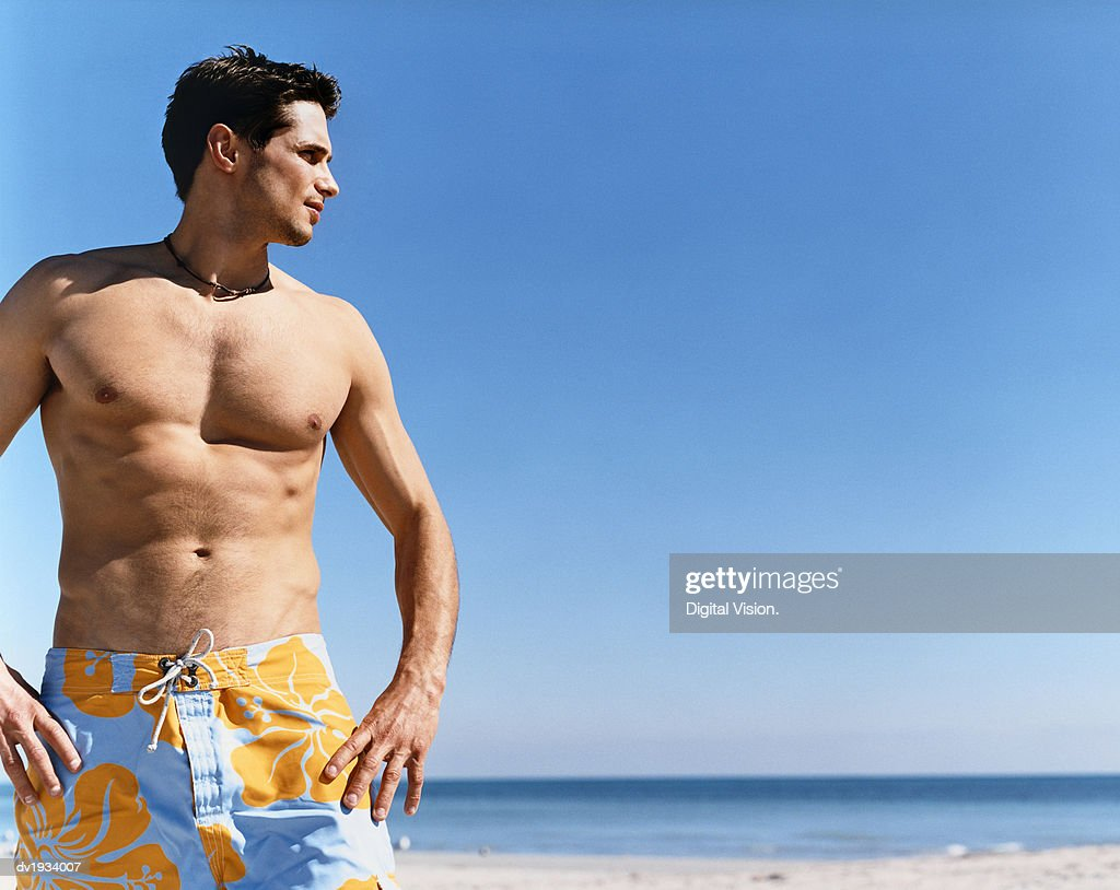 Man Standing on a Beach With His Hands on His Hips and Looking Sideways : Stock Photo