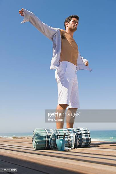 Man standing on a boardwalk with his arm outstretched