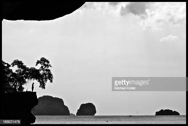 Man standing on a cliff in a contemplative moment over the ocean in Krabi, Thailand in December 2010.