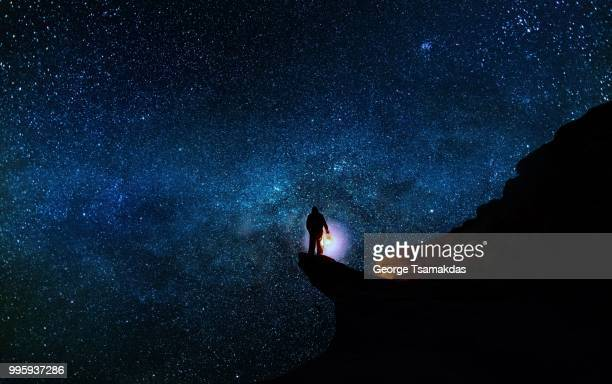 a man standing on a cliff with a starscape behind. - explore stock photos and pictures