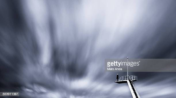 man standing on a diving tower - futurism stock photos and pictures