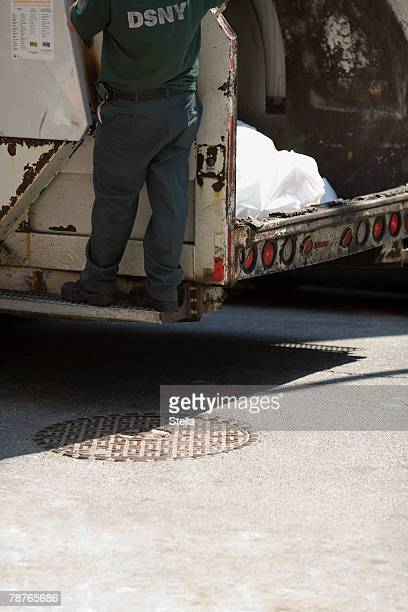 a man standing on a garbage truck - garbage truck stock pictures, royalty-free photos & images