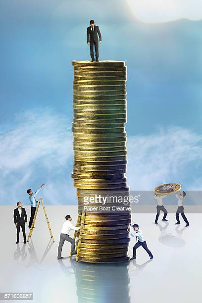 Man standing on a high stack of gold coins