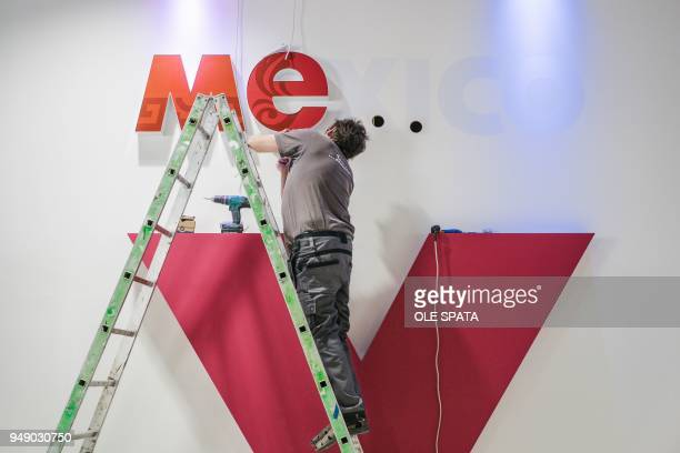 A man standing on a ladder fixes letters of the word Mexico as preparations are under way for the Hannover Messe trade fair for industrial technology...