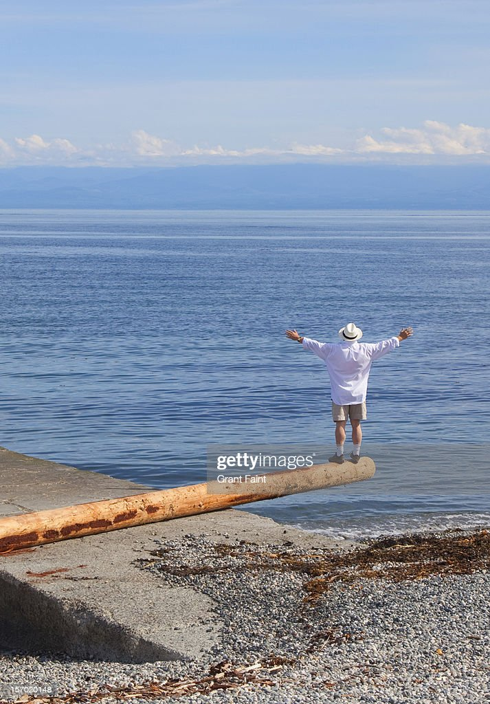 Man standing on a log at the beach : Stock Photo