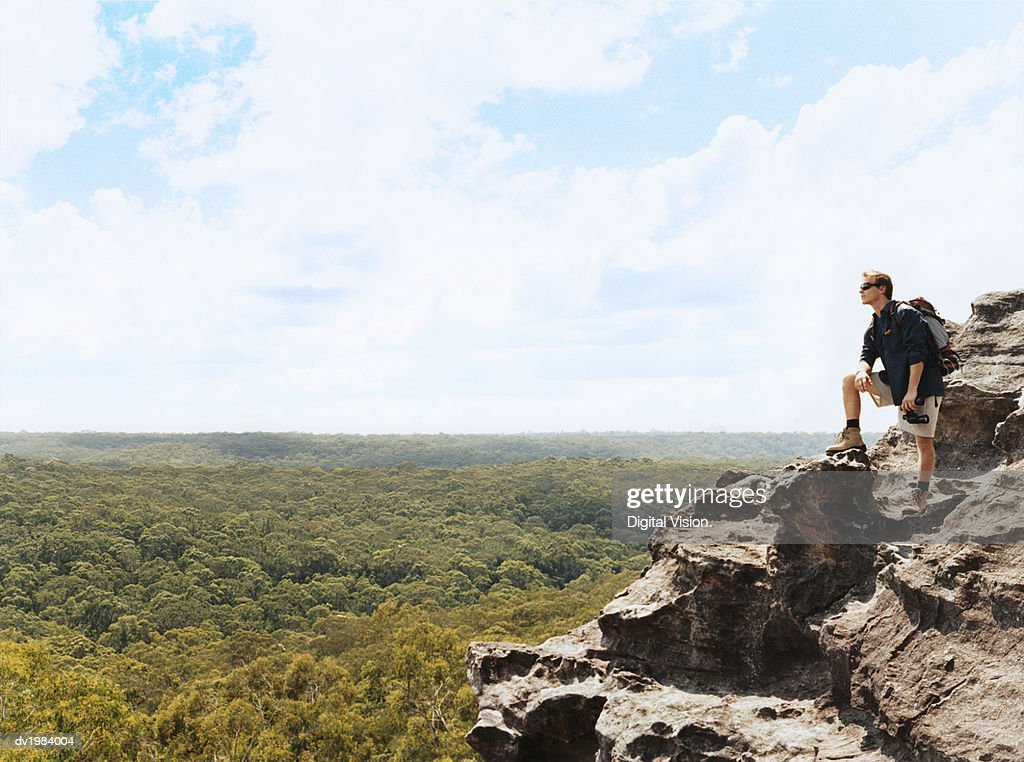 Man Standing on a Mountain Summit Holding a Pair of Binoculars : Stock Photo