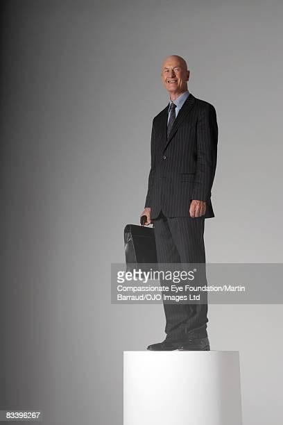 Man standing on a pedestal, holding a briefcase
