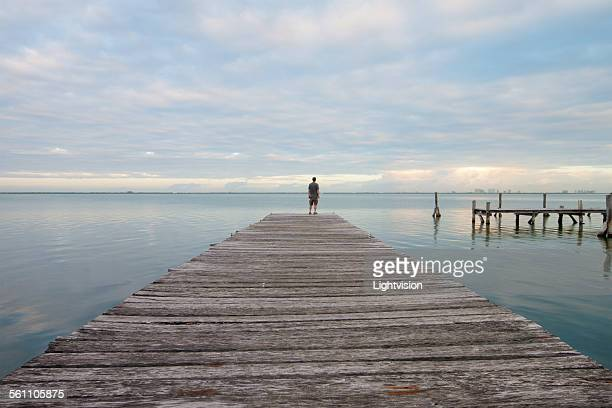 Man Standing on a Pier