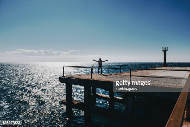 Man standing on a pier with his arms outstretched