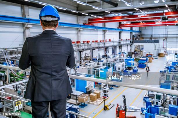 工場の生産ホールを見下ろす上げられたプラットホームに立っている男 - 見渡す ストックフォトと画像