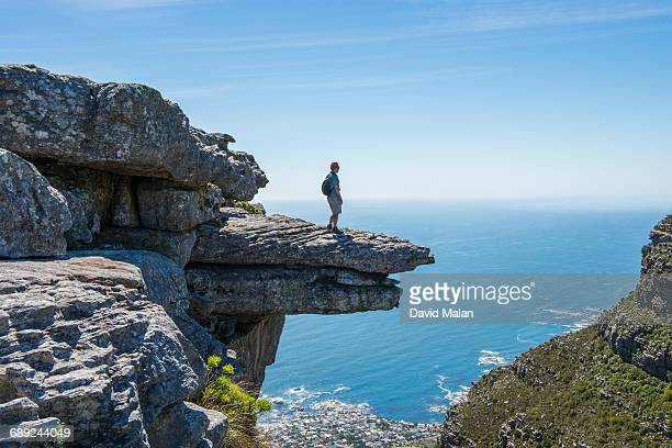 man standing on a rock ledge. - david cliff stock pictures, royalty-free photos & images