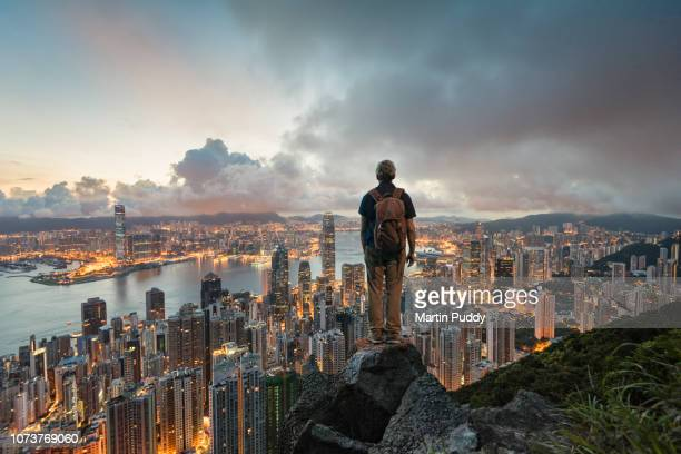 a man standing on a rock overlooking hong kong skyline at dawn, from victoria peak - paesaggio urbano foto e immagini stock