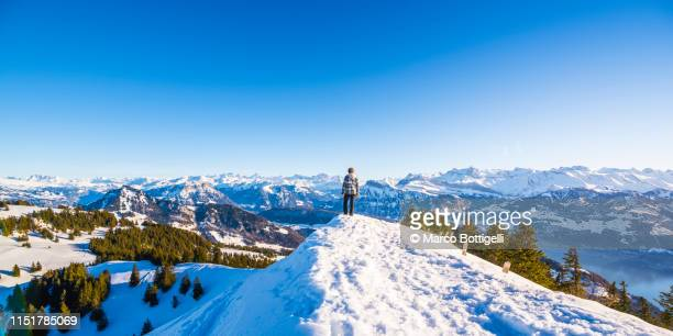 man standing on a snowcapped ridge at sunset, switzerland - mountain ridge stock pictures, royalty-free photos & images