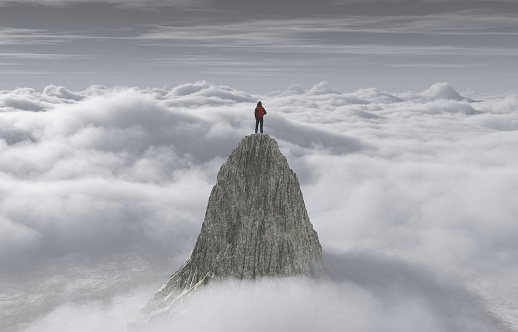 A man standing on a stone cliff over the clouds .Success concept. 966286056