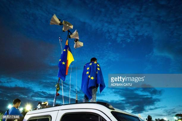 TOPSHOT A man standing on a truck is draped into a flag of Europe as demonstrators gather in front of the Romanian Prime Minister's office building...