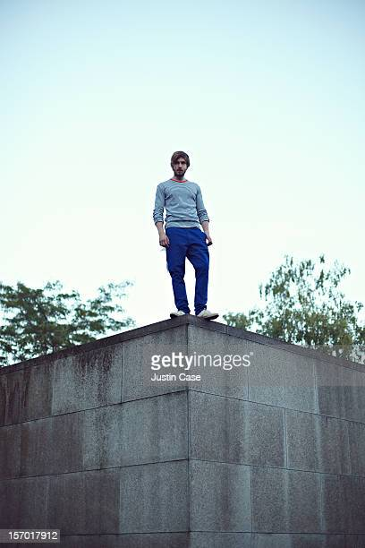 A  man standing on an edge of a wall