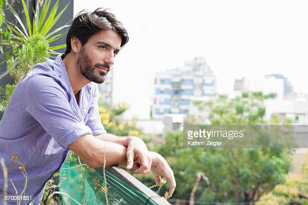 man standing on balcony, looking at cityscape