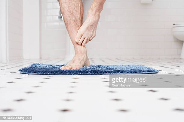 Man standing on bathmat, low section