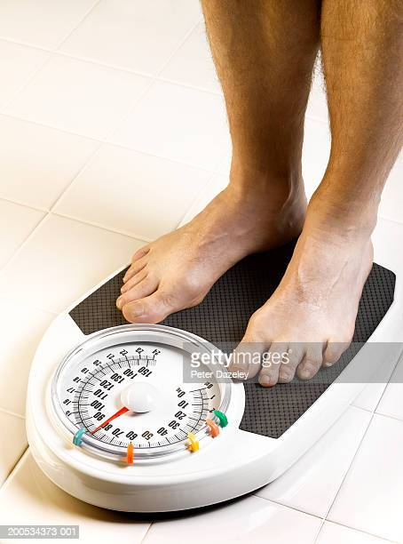 Man standing on bathroom scales, low section