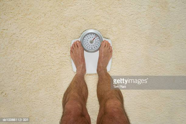 Man standing on bathroom scales, low section, view from above
