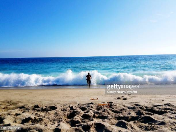 man standing on beach against clear sky - casey nolan stock pictures, royalty-free photos & images
