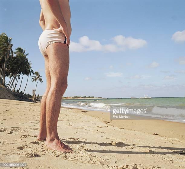 man standing on beach, arms akimbo, low section - calzoncini da bagno foto e immagini stock