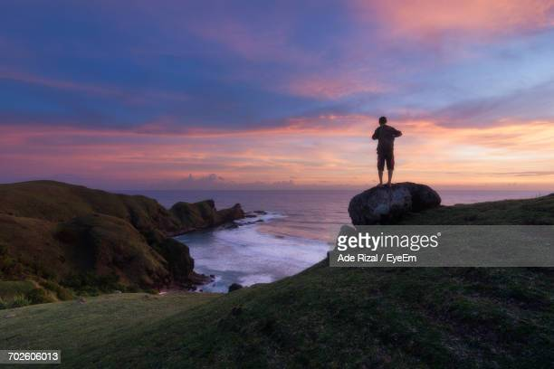 man standing on beach cliff during sunset - ade rizal stock photos and pictures