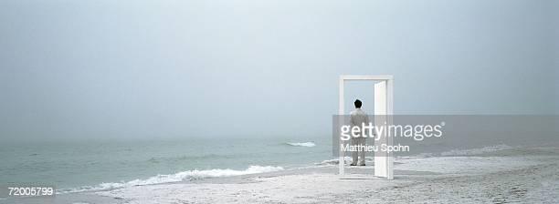 Man standing on beach, framed by doorframe