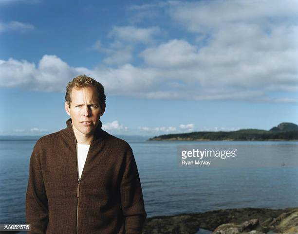 Man standing on beach, high section, portrait (selective focus)