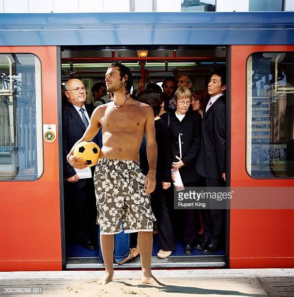 Man standing on beach in front of open doors of busy train