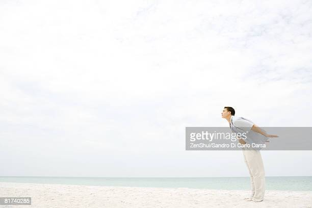 Man standing on beach, leaning into wind, arms behind back and eyes closed