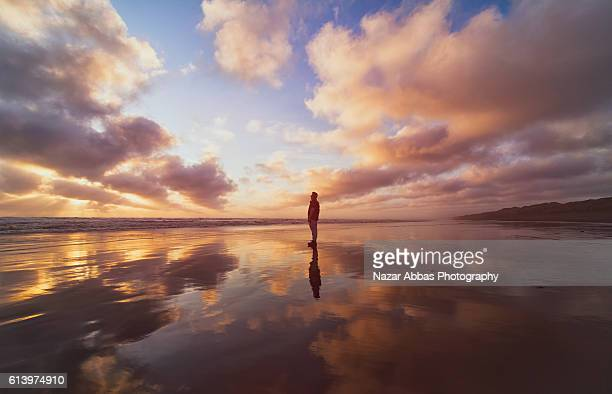 man standing on beach. - spirituality stockfoto's en -beelden