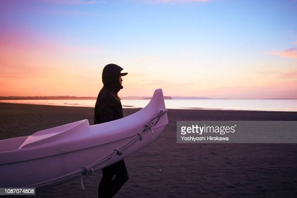 Man standing on beach to lean against canoe at sunrise.