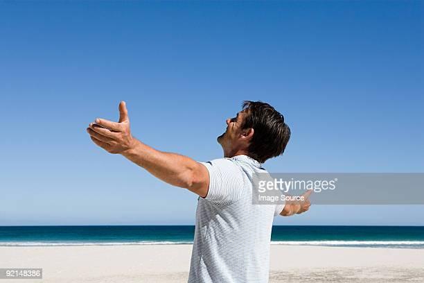 homme debout sur la plage avec les bras écartés - polo t shirt photos et images de collection