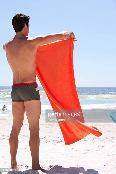 Man standing on beach with holding towel