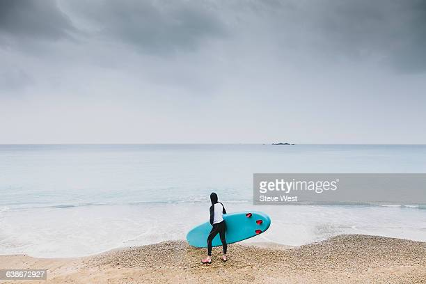 Man standing on beach with Paddleboard (SUP)