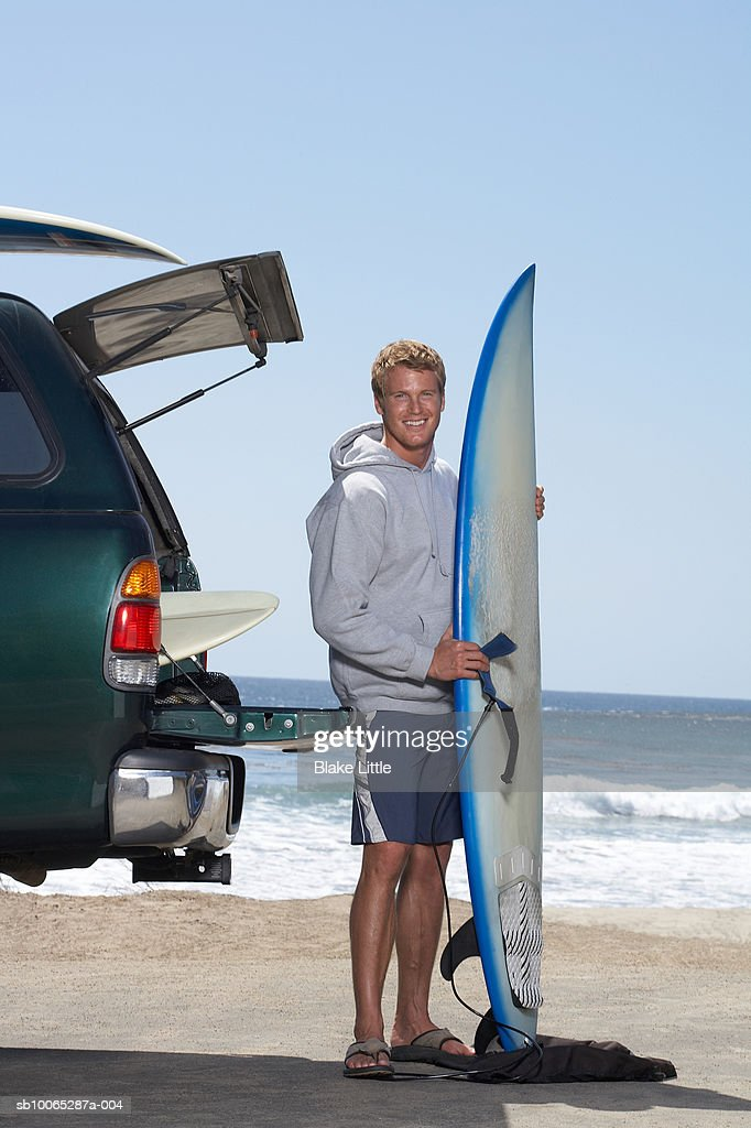 Man standing on beach with surfboard, smiling, portrait : Foto stock
