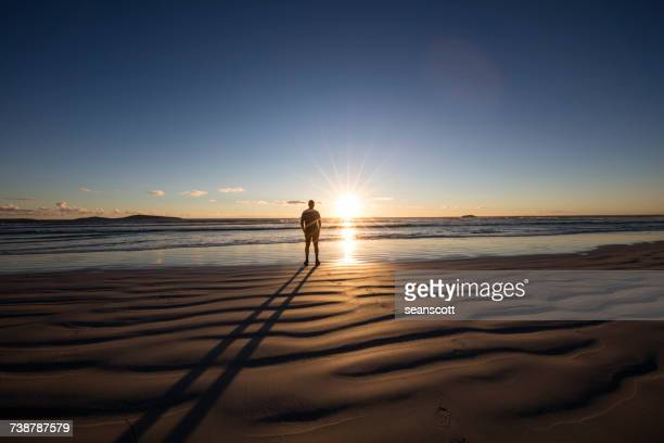 man standing on beech looking at the sunset, western australia, australia - distant stock photos and pictures