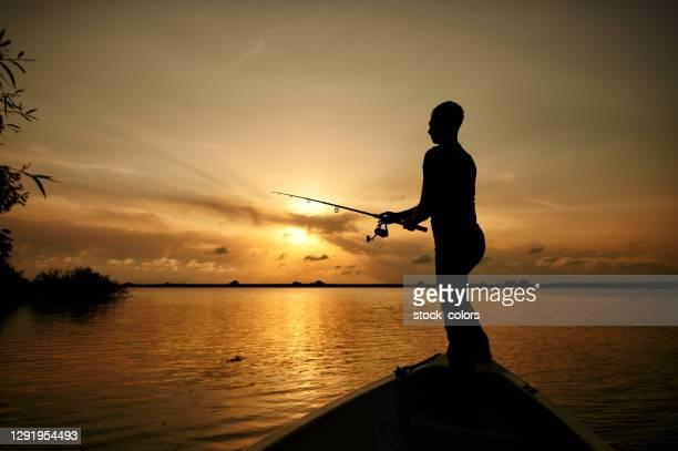 mens die zich op boot het vissen bevindt - vishaak visgerei stockfoto's en -beelden