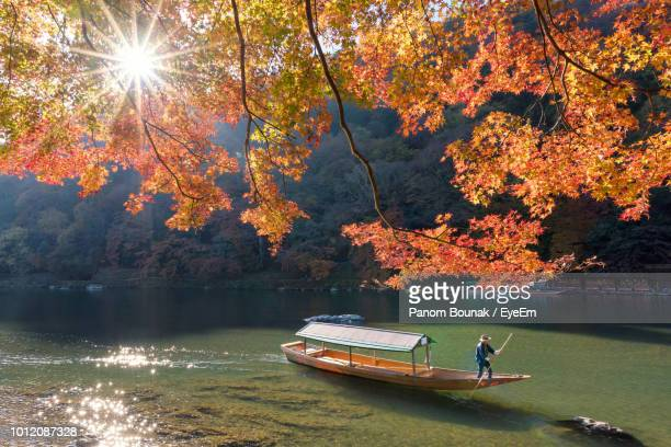man standing on boat in lake against mountain during autumn - kyoto prefecture stock pictures, royalty-free photos & images