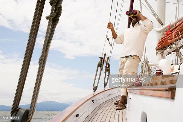 Man Standing on Boat Looking Through Binoculars